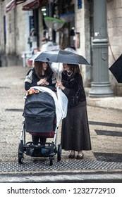 JERUSALEM, ISRAEL - MARCH 9, 2014: Orthodox Jewish woman walk in jewish quarter with children in rainy weather. Jerusalem. Israel