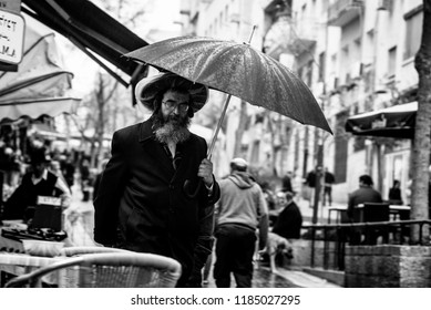 JERUSALEM, ISRAEL - March 9, 2016 - Jews walking with umbrellas and standing in the street of Jerusalem in rainy weather.