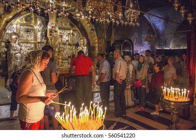 JERUSALEM, ISRAEL - MAY 05, 2015: Faithful lighting candles, inside the church of the Holy Sepulcher