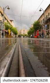 Jerusalem, Israel - May 05, 2020: Rainy Jaffa street, tram railway, generali building