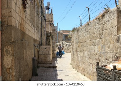 Jerusalem, Israel - May 16, 2018: A man carries garbage bags through the Old City of Jerusalem, Israel.