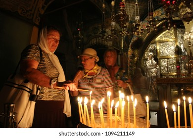 Jerusalem, Israel - May 16, 2018: Three believing women light candles in the Church of the Holy Sepulchre of Jerusalem to honor Jesus, the Son of God.