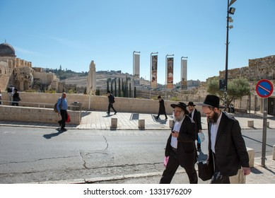 JERUSALEM, ISRAEL - MAY 16, 2018: Haredi ultra orthodox Jews walking on strees of Jerusalem, Mount  of Olives in the background