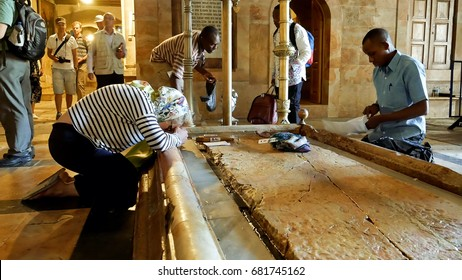 Jerusalem, Israel - May 25, 2017: Prayers at the Stone of Anointing in the Holy Sepulcher Church in Jerusalem. The Church and Empty Tomb are the most sacred places for all Christians people in the world.