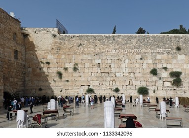 JERUSALEM, ISRAEL - MAY 25, 2018: Group of Jewish people praying as holy due in front of ancient limestone wall known as Western Wall to its connection to the Temple Mount in the Old City of Jerusalem