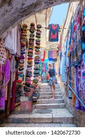 Jerusalem, Israel; May 25th, 2019 - A woman looking at some items in the Muslim quarter of the old city of Jerusalem, Israel.