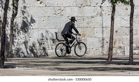 JERUSALEM, ISRAEL - MAY 26: Hassid rides a bicycle past the Jaffa Gate. The Western Wall is the most sacred sites in Judaism, it attracts thousands of devotees every day, on May 26, 2013 in Jerusalem