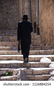Jerusalem, Israel - may 3, 2015: Backlit image of a man of the Hasidic religion, climbing some stairs in the Jewish quarter of the historic city
