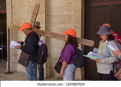 Jerusalem, Israel - May 3, 2019: Pilgrims at the second station of the Via Dolorosa, where Jesus receives His Cross, near facade of the Church of the Flagellation