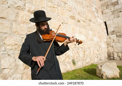 JERUSALEM, ISRAEL - OCT 07, 2014: A jewish fiddler is playing violin on the street near Jaffa gate in Jerusalem