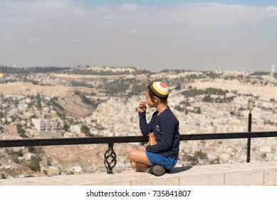 JERUSALEM, ISRAEL - OCTOBER 10, 2017 Jewish religious boy with a skullcap also called kippah sits and looks at Jerusalem.A child eating a snack outside on a sunny day on  white Jerusalem background .