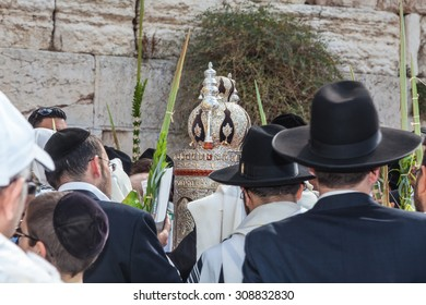 JERUSALEM, ISRAEL - OCTOBER 12, 2014: Morning autumn Sukkot. The area in front of Western Wall of  Temple. Crowd of Jewish worshipers in  wearing prayer shawls. Sefer Torah .