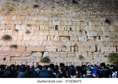 JERUSALEM, ISRAEL - OCTOBER 15, 2014: Worshipers pray at the western wall. The wall is the most sacred site in Judaism outside of the Temple Mount itself.
