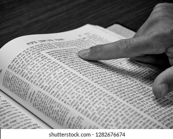 JERUSALEM, ISRAEL - OCTOBER 18, 2018:  Close-up of a a human hand browsing through a Torah commentary and
