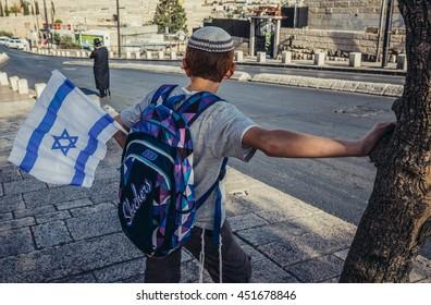 Jerusalem, Israel - October 22, 2015. Israeli boy with national flag waits for the bus in Jerusalem