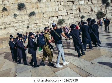 Jerusalem, Israel - October 22, 2015. Group of Orthodox Jews dance  with Israeli soldiers next to ancient limestone wall known as Wailing Wall in the Old City of Jerusalem