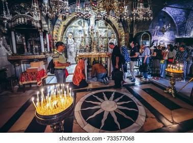 Jerusalem, Israel - October 22, 2015. Pilgrims and tourists visit altar at the traditional site of Calvary (also called Golgotha) inside the Church of the Holy Sepulchre located in Christian Quarter
