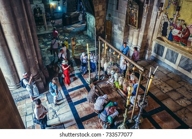 Jerusalem, Israel - October 22, 2015.  Christian pilgrims pray on the Stone of the Anointing inside the Church of the Holy Sepulchre located in Christian Quarter