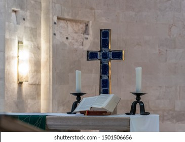 Jerusalem, Israel, September 07, 2019 : Cross, candles and scripture on the table in the Lutheran Church of the Redeemer on Muristan street in the Old City in Jerusalem, Israel