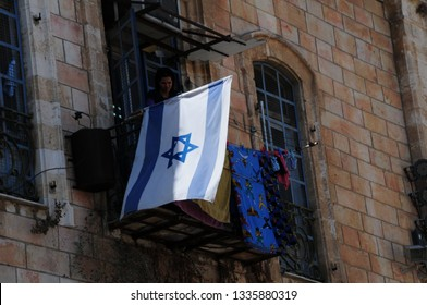Jerusalem / Israel - September 13, 2010: Israeli flag flies next to a balcony in Old Town Jerusalem where a woman hangs laundry to dry.