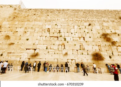 Jerusalem, Israel-March 14, 2017: Jews pray at The Western Wall - where Jews are permitted to pray close to the holiest site in the Jewish faith  which lies behind it, on Temple Mount.