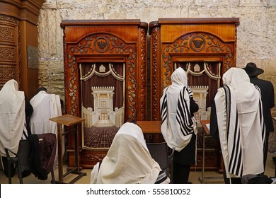 JERUSALEM - JANUARY 2017:  Jewish men wearing prayer shawls at the section of the Western Wall under Wilson's arch, in front of Torah arks depicting the Temple, as seen in Jerusalem circa 2017.