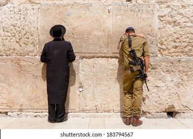 JERUSALEM - JULY 18, 2010: Soldier and orthodox jewish man pray at the western wall, Jerusalem