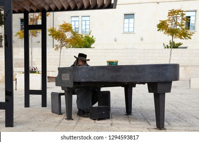 Jerusalem, Kikkar Safra, Israel - December 24, 2018: An ultra orthodox jewish man playing the outdoor piano at Jerusalem squire, Israel
