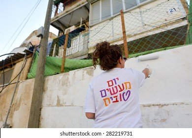 JERUSALEM - MAR 25 2015:Israeli volunteer paint a wall in poor neighborhood in Jerusalem,Israel on Good Deeds Day. In 2015 930,000 participants from 61 countries took part in 11,000 projects worldwide
