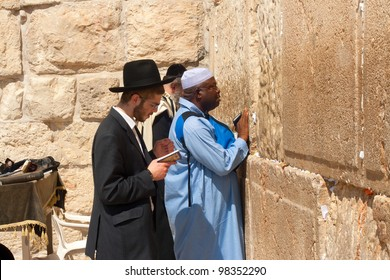 JERUSALEM - MARCH 09: An religious tourists from Africa and religious Jew, wearing a prayer shawl draped, prays near the Wailing Wall in the Old City of Jerusalem, March 09, 2007.
