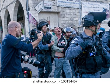 JERUSALEM - MAY 20 : Israeli policemen detain a Palestinian demonstrating against thousands of Israeli right wingers commemorating Jerusalem day with a march to Jerusalem old city on May 20 2012