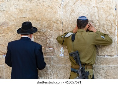 JERUSALEM - MAY 6: An unidentified man and Israeli soldier pray at the Western Wall, Judaism's holiest site, in the Old City of Jerusalem on May 6, 2016.