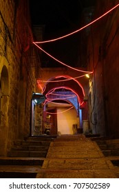 Jerusalem at night Israel, Jerusalem: The streets of the old city at night. Christmas garlands.Ukly streets, red lights, yellow walls.