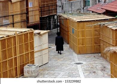JERUSALEM - OCT 20:Orthodox Jewish man walks between Sukkah booths during Sukkot  Jewish holiday in Mea Shearim on October 20 2005 Jerusalem, Israel.