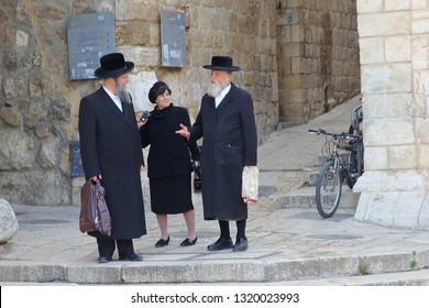 JERUSALEM OLD CITY, ISRAEL - February 14, 2019. Orthodox Jewish men and woman with traditional black hats and clothing are talking together in outdoor street of the Jewish Quarter.