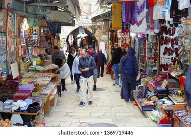 JERUSALEM OLD CITY, ISRAEL - February 14, 2019. Men and women are shopping in narrow street with a display variety of shops and stores in the souk market.