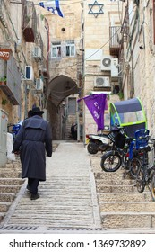 JERUSALEM OLD CITY, ISRAEL - February 14, 2019. Orthodox Jewish man is walking in narrow street with stairs, parked bikes, ancient houses, Israeli flag and star of David on the wall.