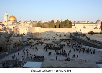 Jerusalem / Palestine - February 18th 2014: Jews worshipping at the Wailing Wall surrounded by Israeli Police. Religious landmark for Judaism. Dome of the Rock and Al-Aqsa Mosque seen in distant.