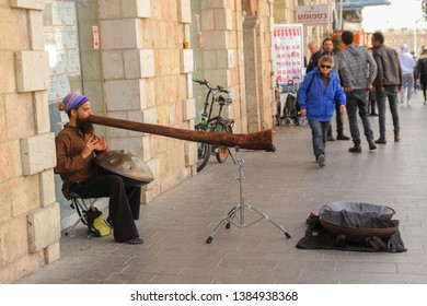Jerusalem/Israel - 09.03.2018: Musician plays didgeridoo and hang drum at the same time. Jaffa street