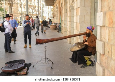 Jerusalem/Israel - 09.03.2018: Musician plays didgeridoo and hang drum at the same time. Jaffa street. Guy in the traditional jewish clothes looks with interest.