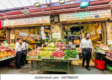 Jerusalem/Israel- August 16, 2016: A crowd of men shopping for vegetables in a shop in the Mahane Yehudah market in Jerusalem, Israel