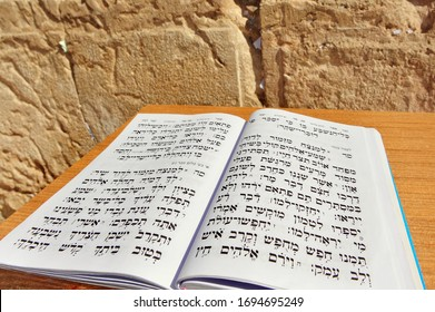 JERUSALEM-NOV 05 2010:King David Book of Psalms in Hebrew against the Wailing Wall. The Messiah will be a patrilineal descendant of King David, and will gather the Jews back into the Land of Israel.