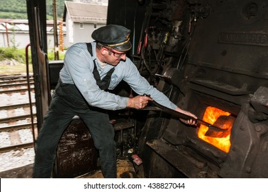 JESENICE, SLOVENIA - JUNE 11th 2016: Sooty stoker shoveling coal in the furnace of the steam engine. Train is carrying tourists on the old Bohinj railway.
