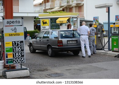 JESOLO, ITALY - AUGUST 26, 2013: Old Lancia Thema Station Wagon estate car on the petrol station. Italian petrol and diesel prices on Agip fuel pump.