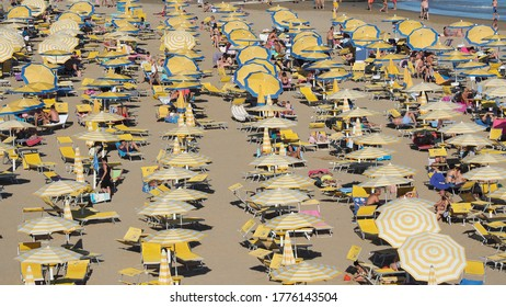 Jesolo, Italy, July 12, 2020. Beach umbrellas and sun beds at Italian sandy beaches. Peak season, many people and a lot of mess. Adriatic coast. Yellow and white umbrellas