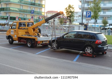 JESOLO, ITALY - JUNE 14, 2012: Italian tow truck at work. Volkswagen Golf car evacuation.