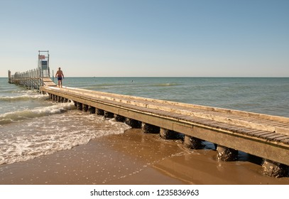 Jesolo Lido / Italy - August 16 2018: Retired old man walking on a landing stage on Adriatic Sea at sunrise in summer, Venice, Veneto, Italy