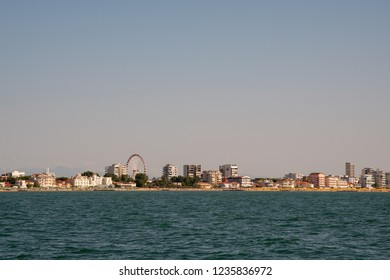 Jesolo Lido / Italy - August 16 2018: View from the sea of the coastal city of Jesolo Lido with big wheel and skyscrapers, Veneto