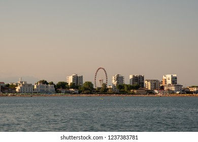 Jesolo Lido / Italy - August 16 2018: City view from the sea with panoramic wheel and skyscrapers at sunset
