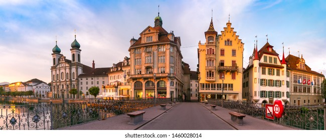 Jesuit Church along the river Reuss, traditional frescoed building and Reussbrucke bridge at sunrise in Old Town of Lucerne, Switzerland